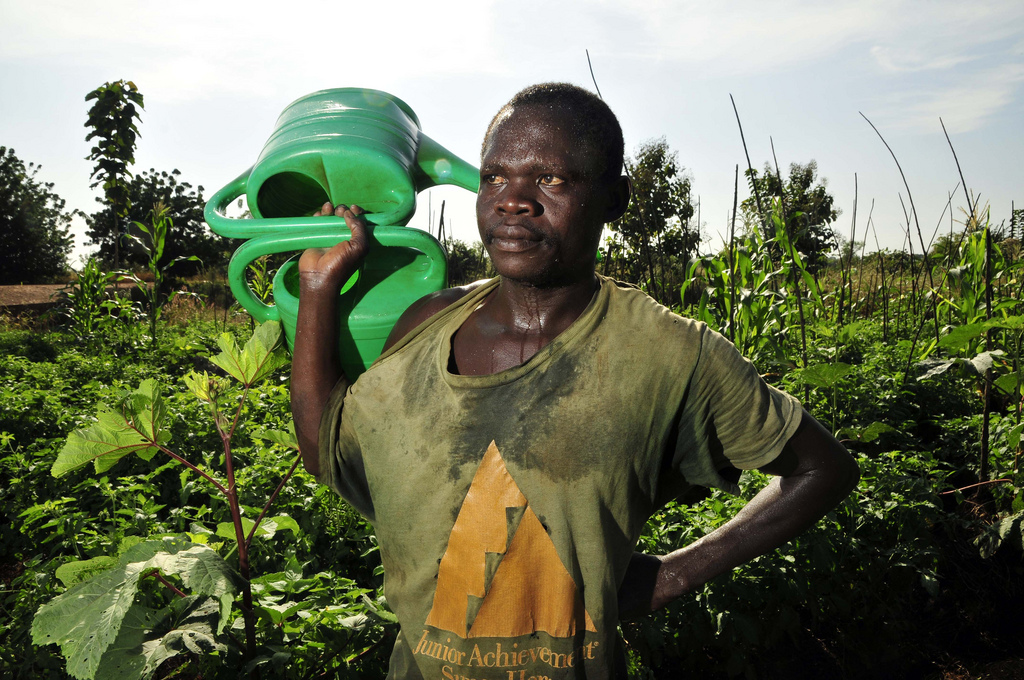 A man holding a watering can in Mozambique