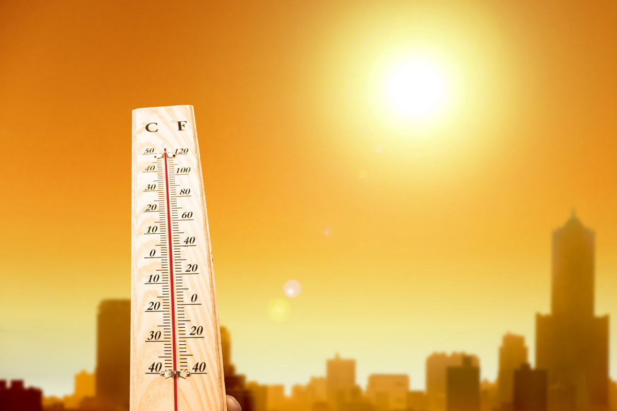 thermometer with bright sun and skyline in background