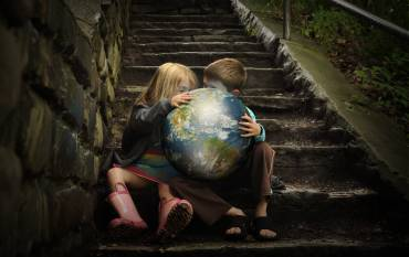 two kids holding the Earth in their hands