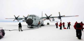 Reseach team in front of airplane on the ice