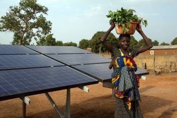 Woman standing next to a solar panel with a basket