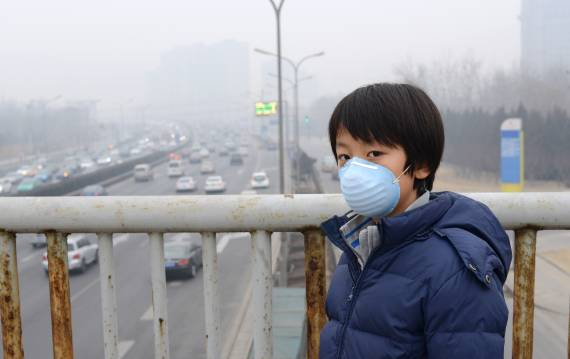 Child wears mouth mask in Beijing with air pollution in background.