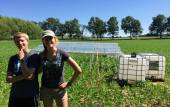 Students standing in front of solar panels in a field