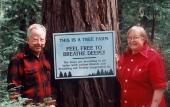 George and Anita Thompson next to a coastal redwood