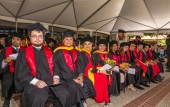 students seated at commencement in caps and gowns