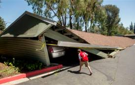 A boy looking at cars in a collapsed garage.