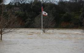 flag pole sticking up above flood waters