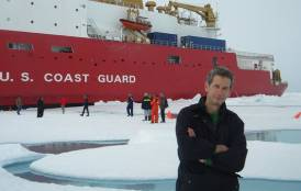 Kevin Arrigo standing in front of a U.S coast guard ship