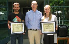 Two students holding their awards