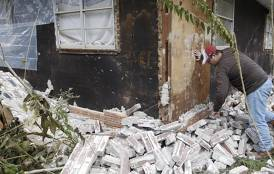 Sparks, Oklahoma resident Chad Devereaux examines earthquake damage to his home.