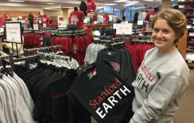 Student holding a Stanford Earth t-shirt in the bookstore