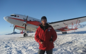 Dustin Schroeder stands in front of airplane in Antarctica