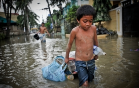 Child wades through flood water. Credit: Asian Development Bank/Flickr