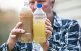 Ray Kemble holds two samples of well water from his neighborhood in Dimock, PA.