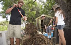 A man and a women working on a compost pile