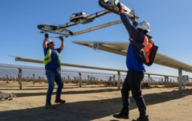 Workers at a solar station in the Mojave Desert attach a robot to clean panels.