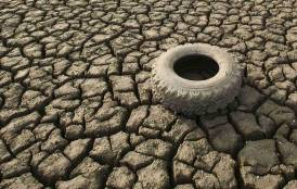 Tire over dry, cracked earth