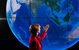 Pam Matson in front of a screen with a blue globe