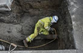 Pipeline worker in pit.