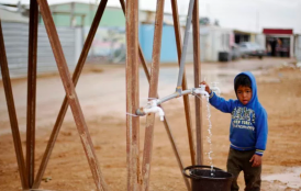 young boy collecting water