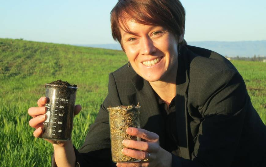 Kate Maher hold two beakers of soil.